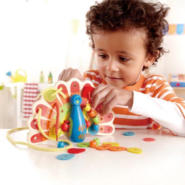 Kind spielt mit dem Fädelspiel Pfau